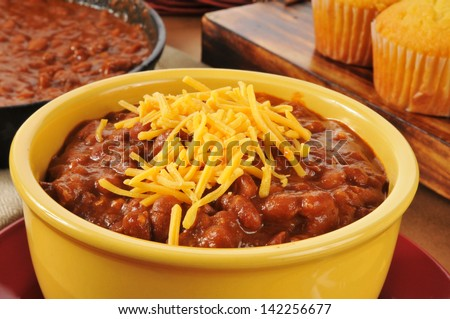 A bowl of chili con carne with shredded cheddar cheese - stock photo