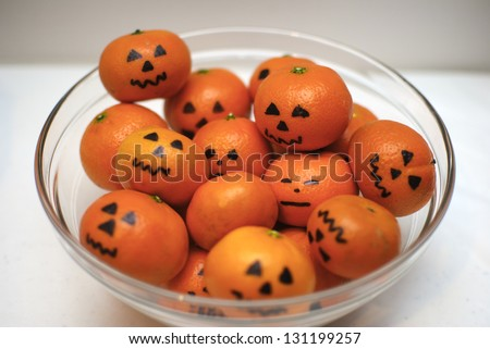 A bowl of clementine oranges decorated to look like jack-o-lanterns. - stock photo