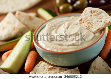 A bowl of delicious homemade baba ganoush dip with pita, carrots, cucumber, zucchini, and olives. - stock photo