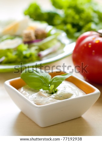 A bowl of dip with salad on background.  Shallow depth of field, selective focus - stock photo