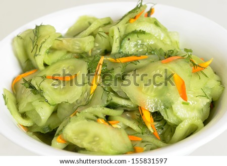 A bowl of fresh and healthy cucumber salad with stripes from carrots. Image taken close up over white. It's a vegetarian and vegan meal. - stock photo