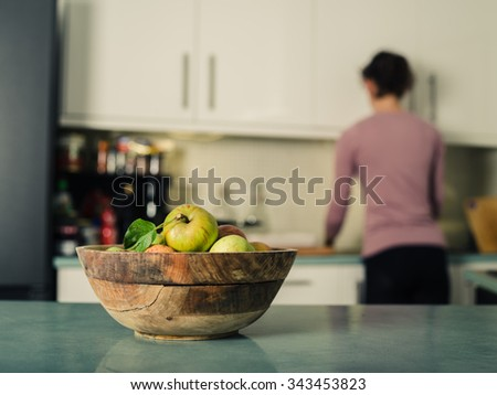 A bowl of freshly picked green apples on a table in the kitchen with a woman doing housework in the background - stock photo