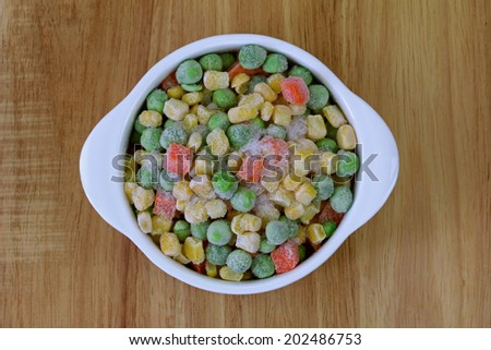 A bowl of frozen diced vegetable (corn, peas, carrots) on a wooden background - stock photo