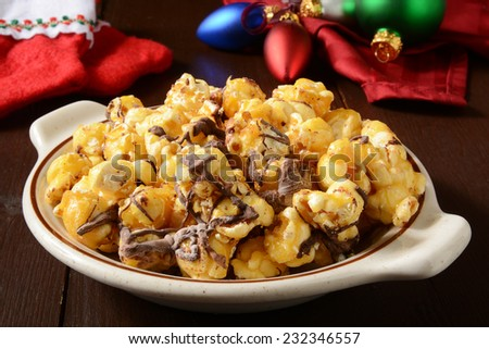 A bowl of gourmet chocolate caramel popcorn with Christmas ornaments and stockings - stock photo