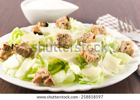 A bowl of green salad with yogurt sauce, cheese and toast on a wooden table. - stock photo