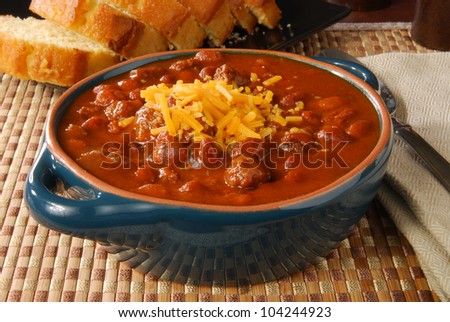 A bowl of hot chili with melted cheese - stock photo