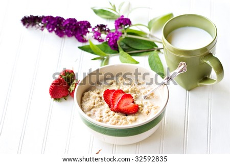 A bowl of hot oatmeal with fresh strawberries cut into the shapes of hearts for a heart healthy breakfast with a cup of milk. Shallow DOF. - stock photo