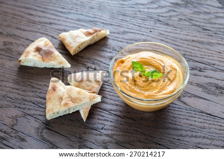 A bowl of hummus with pita slices - stock photo