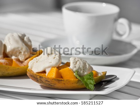 A bowl of ice cream and mango on a white wooden Desk - stock photo