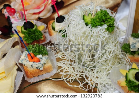 A bowl of long curly cheese on party table - stock photo