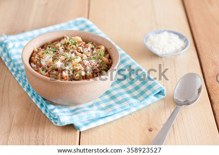 A bowl of macaroni with ground beef, tomatoes and parmesan - stock photo