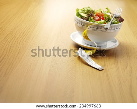 A bowl of mixed salad with a tape measure for healthy eating on a wooden background with copy space. - stock photo