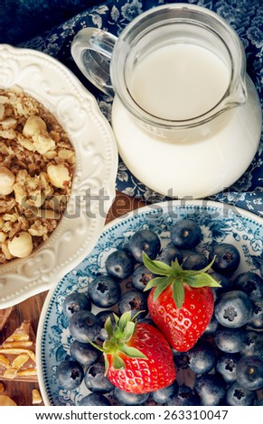 A bowl of muesli with blueberries, strawberry, nuts, chocolate and with milk on a wooden table, healthy breakfast with cereals - stock photo