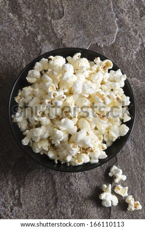 A bowl of popcorn on a dark background - stock photo