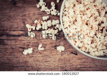 A bowl of popcorn on a wooden table - stock photo