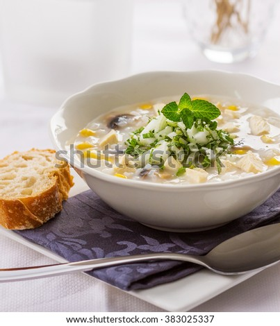A bowl of rice, chicken and corn soup served with raw onions, parsley and mint leaves. - stock photo