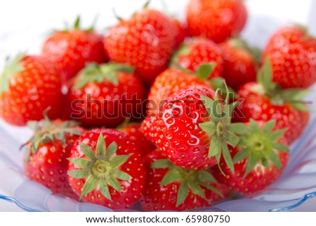 A bowl of ripe and red strawberries ready to be eaten. - stock photo