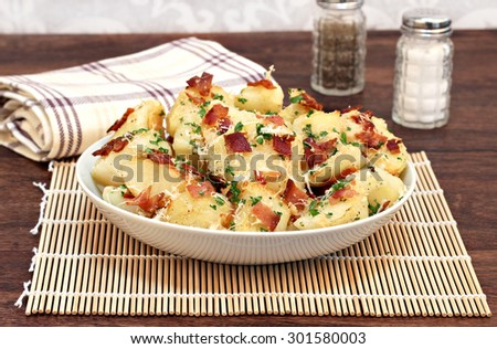 A bowl of roasted garlic, bacon and parmesan potatoes garnished with parsley bits. - stock photo
