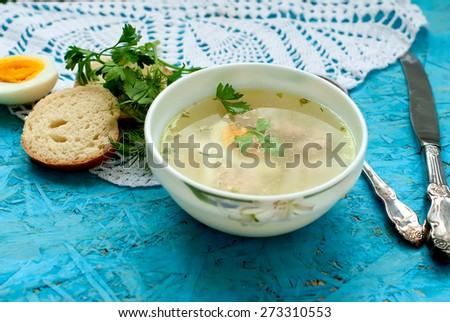 a bowl of soup with meatballs and half eggs with parsley on a wooden tray - stock photo