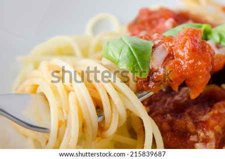 A bowl of spaghetti pasta, tomato sauce and basil leaf with cheese, with close-up of raised fork in foreground, wrapped in spaghetti and dipped in sauce.   - stock photo