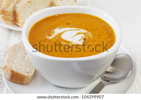 A bowl of spicy pumpkin soup, swirled with coconut cream. - stock photo