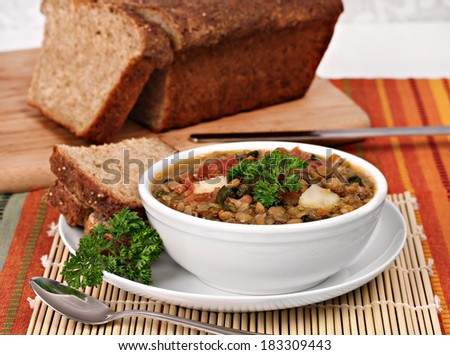 A bowl of spinach, lentil soup garnished with parsley with a side of fresh quinoa bread. - stock photo