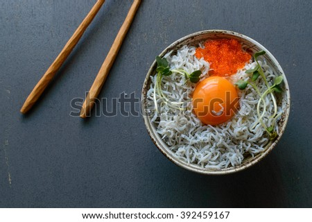 a bowl of steamed rice topped with small sardines, an egg Yolk, flying fish roes and garnished with kaiware sprouts - stock photo