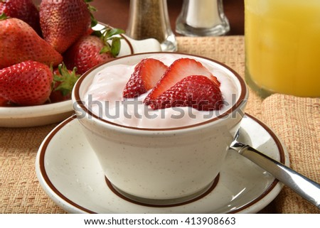 A bowl of strawberry yogurt with a glass of orange juice - stock photo