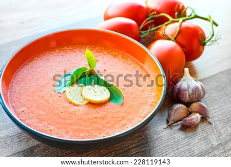 A bowl of tomato soup gaspacho with basil and crackers - stock photo