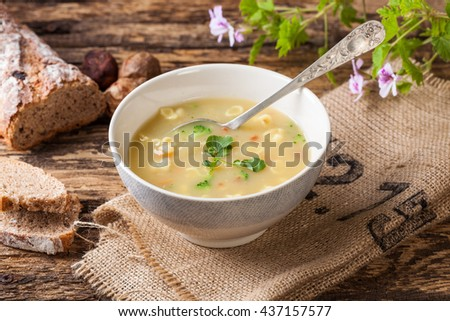 A bowl of vegetable soup with tomato, onion, broccoli and pasta - stock photo