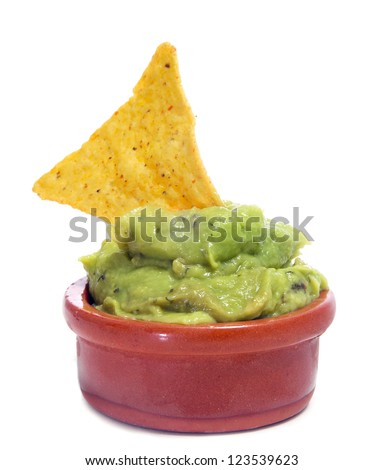 a bowl with guacamole and a nacho on a white background - stock photo