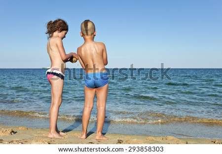 A boy and a girl, about 7 years old, back to dthe camera, sharing time on an emty beach in the summer. - stock photo