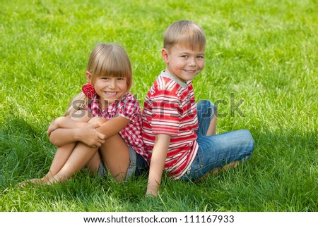 A boy and a girl are sitting together on the grass - stock photo