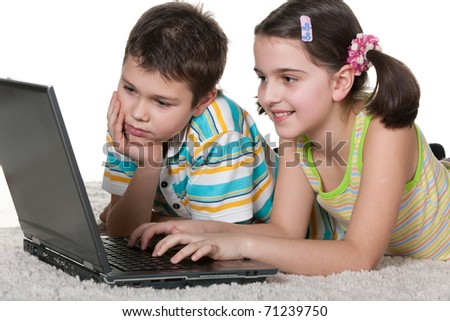 A boy and a girl are studying using a laptop; isolated on the white background - stock photo
