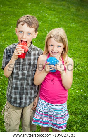A boy and a girl eat snow cones together. - stock photo