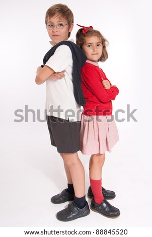 A boy  and little girl back to back with annoyed expressions - stock photo