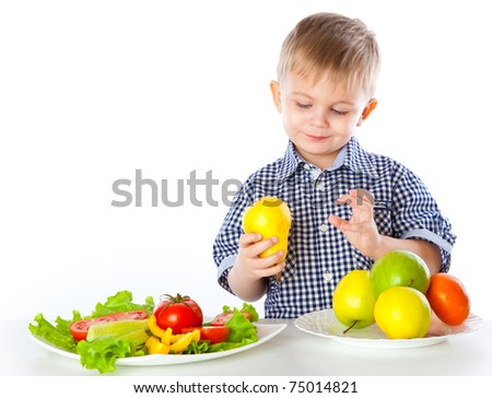 A boy and plates of vegetables and fruit. Isolated on a white background - stock photo