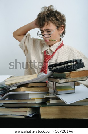 A boy behind a fully covered desk - stock photo