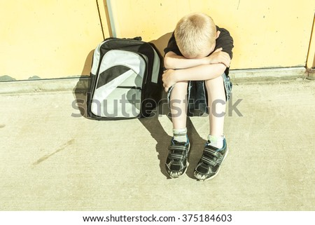 A boy bullying in school playground - stock photo