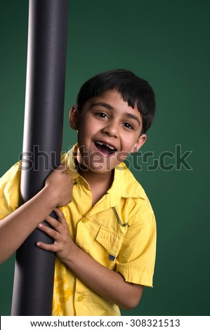 A boy clinging to a pole - stock photo