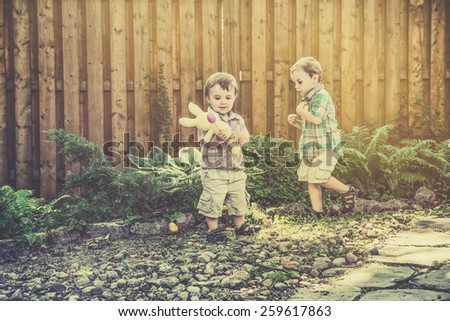 A boy collects Easter eggs during an egg hunt while his younger brother holds a yellow bunny.  Filtered for a retro, vintage look. - stock photo