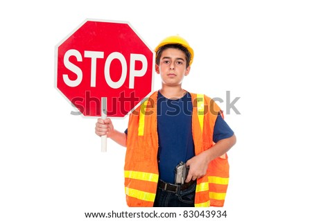 A boy directs traffic using a stop sign and a gun - stock photo
