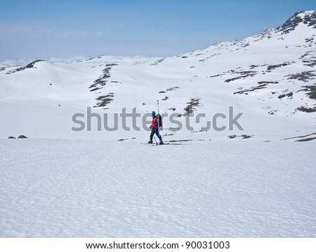 A boy doing a high mountain downhill skiing backwards in the norwegian mountain at easter - stock photo