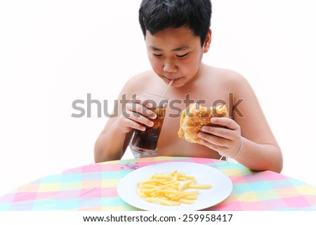 A boy drinking a sweet cold beverage from a soda cup and hamburger in his hand and chips - stock photo