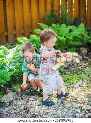 A boy finds golden Easter eggs during an egg hunt while his little brother plays with a plush toy bunny rabbit outdoors in a garden.  Part of a series. - stock photo