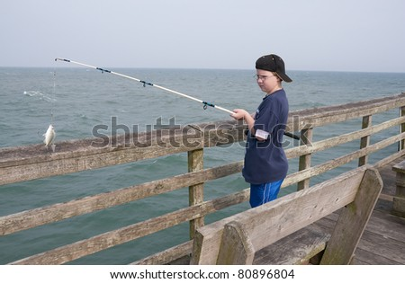 A boy fishing off a pier at the ocean - stock photo