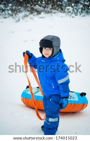 A boy having fun riding a snow tube - stock photo