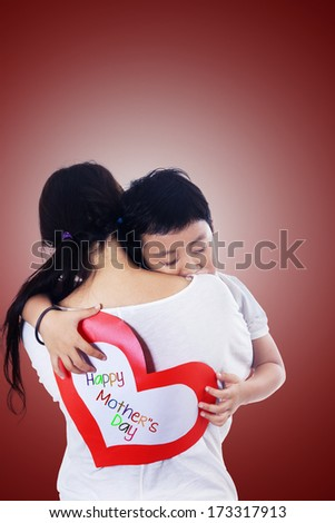 A boy hugging his mother on Mother's Day. Red background. - stock photo