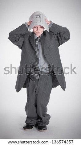A boy in a big jacket is covered papers - stock photo