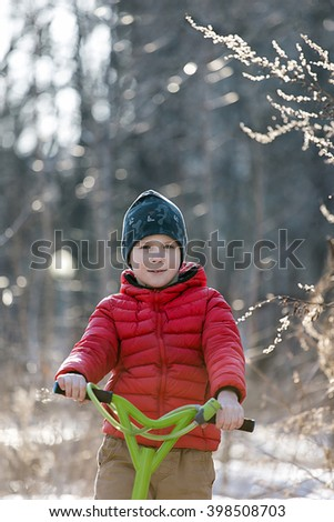 A boy in a red jacket on a scooter in a park in early spring. Sunny spring day - stock photo